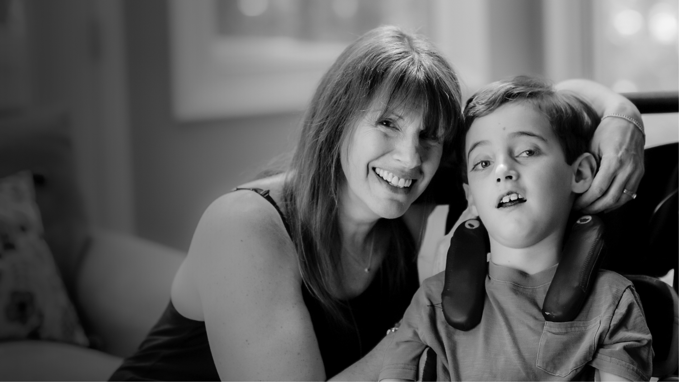 Black and white photo of mother with son with Canavan disease in wheelchair